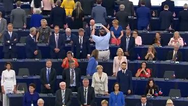Europosłowie partii Brexit wysłuchują 'Ody do radości' stojąc tyłem. Europosłowie z Polski Anna Zalewska i Witold Waszczykowski siedzą, Jacek Saryusz-Wolski robi zdjęcie tabletem