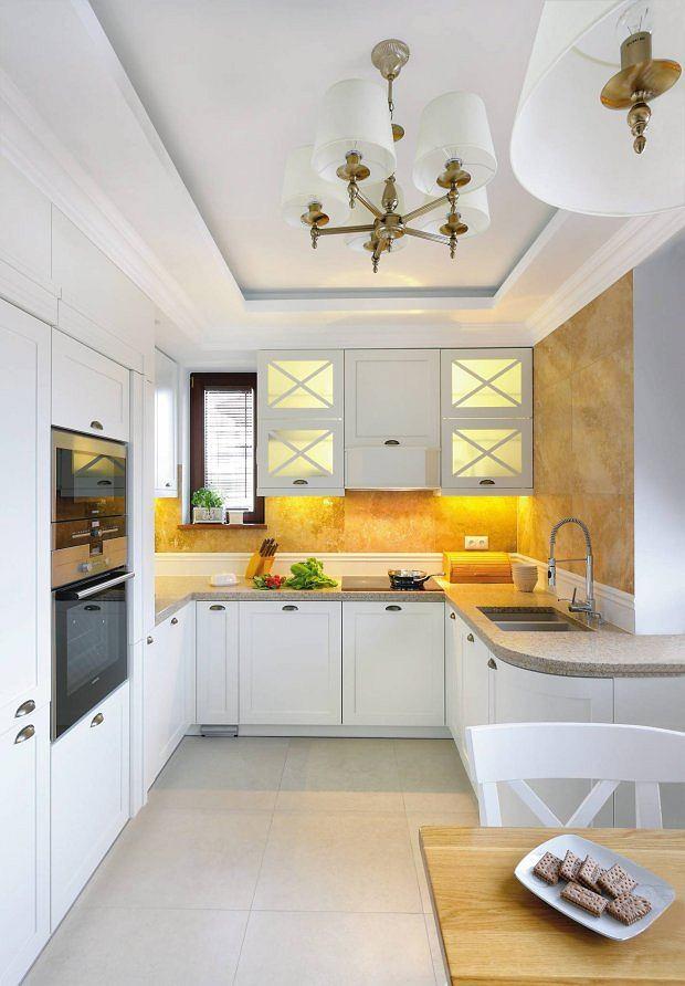 NATURALNY KAMIEŃ. Coraz częściej w naszych kuchniach płytki ceramiczne są zastępowane naturalnym kamieniem. Tutaj położono na ścianie płyty trawertynu (60 x 60 cm). Wzdłuż blatu zamontowano ceramiczne cokoły, które zdobią i chronią ścianę.