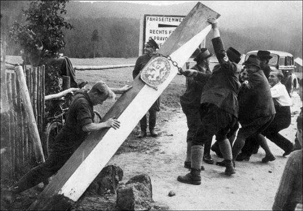 Niemieccy mieszkańcy terytorium Czech przewracają czeski znak graniczny na granicy czesko - niemieckiej, październik 1938 r.