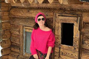 Katarzyna Cichopek stoi na tle drewnianego domku. My zakochaliśmy się w jej spódnicy w kwiaty w góralskim stylu!