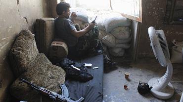 Podczas gdy Zachód zastanawia się, czy to reżim Baszara el-Asada użył broni chemicznej w Damaszku, siły opozycji nie składają broni. W dużych miastach Syrii codziennie dochodzi do starć rebeliantów z siłami rządowymi. Na zdjęciu członek Wolnej Armii Syrii w zaimprowizowanym punkcie obserwacyjnym. W przerwie pomiędzy kolejną akcją w Aleppo z krótkofalówką w dłoni pali papierosa i obserwuje w wstawionym w okno lustrze ruchy wojska lojalnego wobec prezydenta Asada