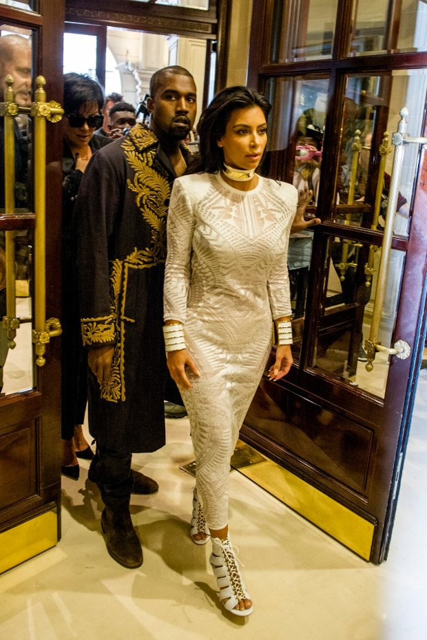 Kim Kardashian and her husband U.S rap artist Kanye West arrives at the Balmain Spring/Summer 2015 ready-to-wear fashion collection, in Paris, France, Thursday, Sept. 25, 2014. (AP Photo/Zacharie Scheurer)