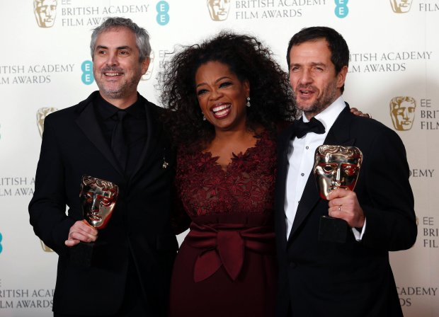 "Director Alfonso Cuaron (L) and producer David Heyman pose with Oprah Winfrey after winning Outstanding British Film for ""Gravity"" at the Royal Opera House in London February 16, 2014. REUTERS/Suzanne Plunkett (BRITAIN - Tags: ENTERTAINMENT)"