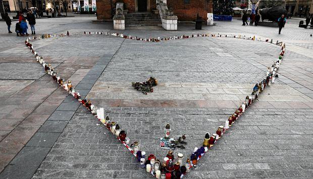 Znicze ustawione w kształt serca przed wieżą ratuszową w Krakowie, na której zawisł napis 'Kraków myślami z Gdańskiem'