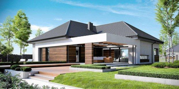 Projekt domu parterowego z belkowaniem nad wejściem i dużym tarasem. Wyjątkowa elewacja łącząca płyty betonowe, biały tynk oraz szlachetne drewno tworzy niepowtarzalną oprawę domu. Maksymalne wykorzystanie przestrzeni umożliwiło wydzielenie bardzo dużej, reprezentacyjnej strefy dziennej