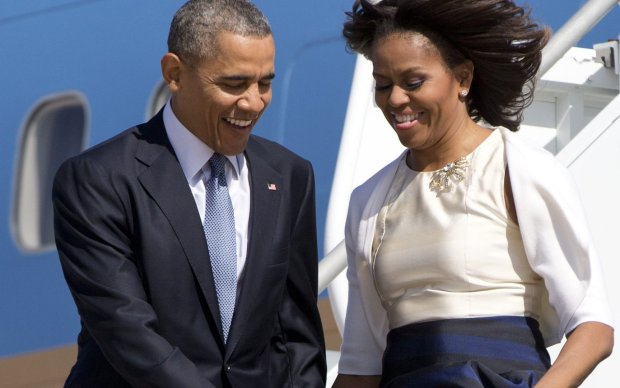 First lady Michelle Obama's dress is caught up in the wind as she and President Barack Obama arrive at Austin-Bergstrom International Airport on Air Force One, Thursday, April 10, 2014, in Austin, Texas, en route to the LBJ Presidential Library to attend a Civil Rights Summit to commemorate the 50th anniversary of the signing of the Civil Rights Act. (AP Photo/Carolyn Kaster)