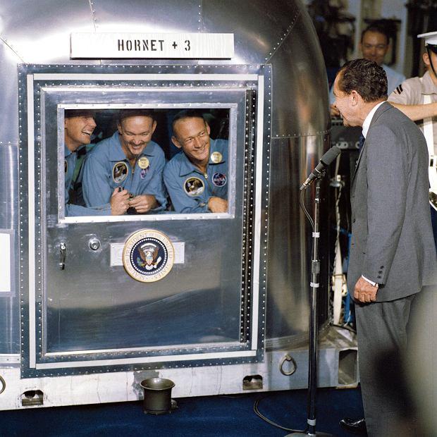 Prezydent Richard Nixon wita astronautów na pokładzie lotniskowca 'USS Hornet'. Chwilę wcześniej ich kapsuła wodowała na Oceanie Spokojnym. Rozmawiają przez szybę, bo zdobywcy Księżyca przechodzą kwarantannę