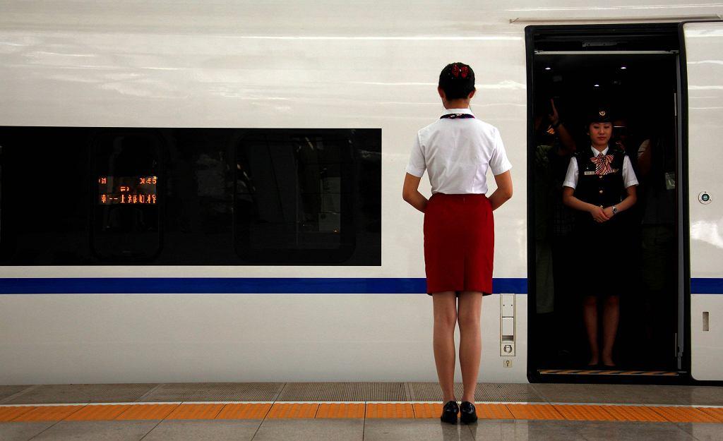 Konduktorka stoi w drzwiach pociągu z Pekinu do Szanghaju.