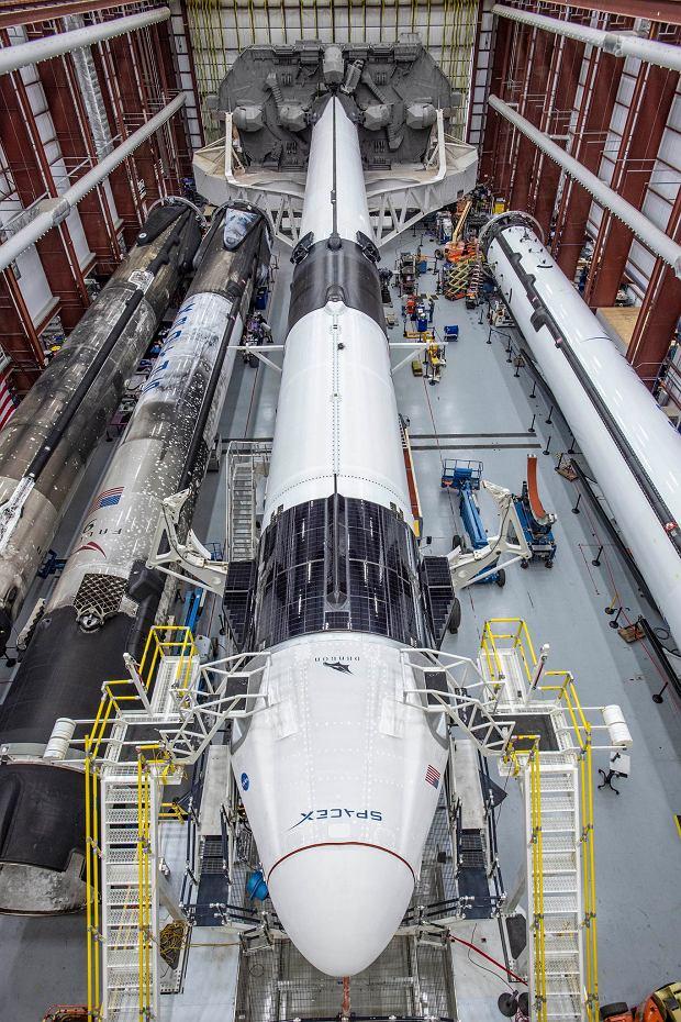 Wnętrze hangaru SpaceX przy wyrzutni 39A. W środku gotowa do wytoczenia rakieta Falcon 9 ze statkiem Crew Dragon. Po lewej dwa pierwsze stopnie rakiety Falcon 9 po powrocie z misji, szykowane do kolejnej