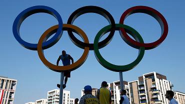 Ukraiński bokser Aleksander Usik wspina się po olbrzymim logo igrzysk