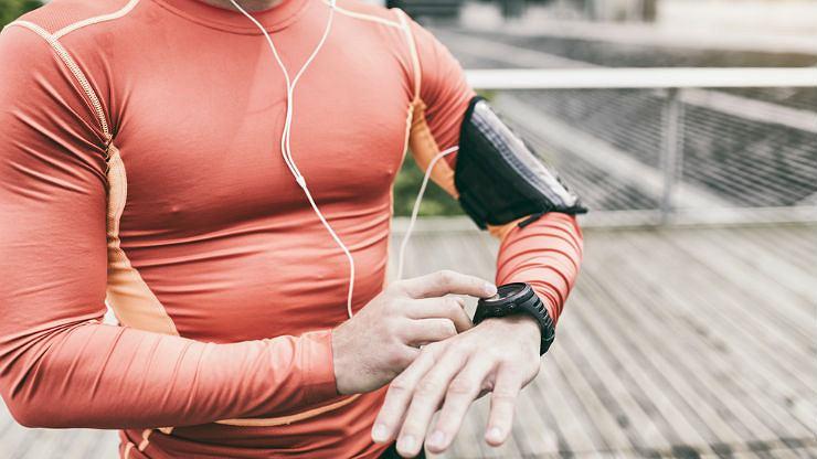 Wysportowany mężczyzna z zegarkiem sportowym i etui na telefon na ramieniu