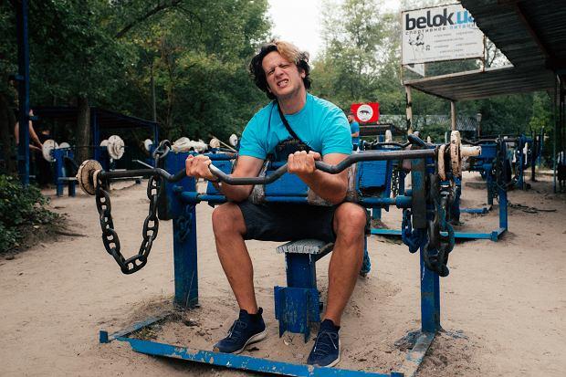 Krzysztof w siłowni na świeżym powietrzu urządzonej z materiałów z recyklingu.