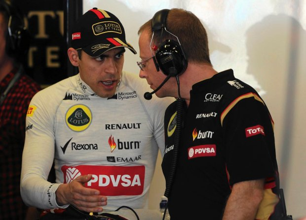 Lotus driver Pastor Maldonado, left, of Venezuela chats with a technician in his garage during the first practice session for the Australian Formula One Grand Prix at Albert Park in Melbourne, Australia, Friday, March 14, 2014. (AP Photo/Rob Griffith) SLOWA KLUCZOWE: f1autoz14
