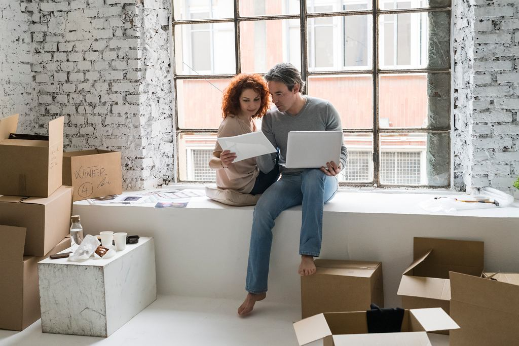 Couple moving into industrial style apartment, sitting on window ledge looking at photograph