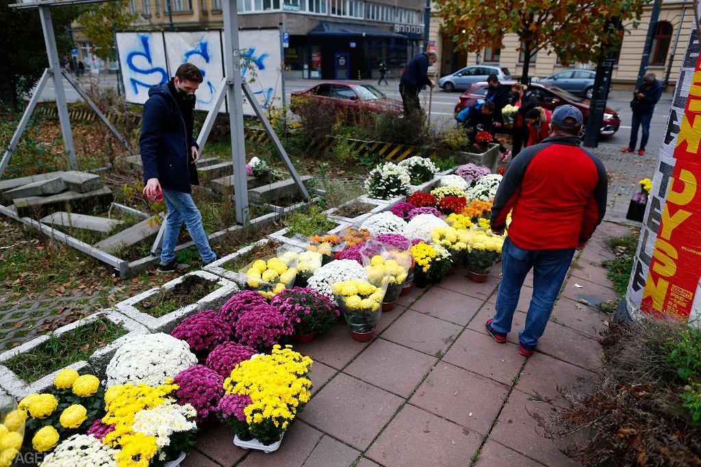 31.10.2020. Łodzianie sadzą przy ul. Piotrkowskiej chryzantemy zakupione przy cmentarzach. To akcja pomocy przedsiębiorcom, którzy stracili finansowo z powodu nakazu zamknięcia nekropolii