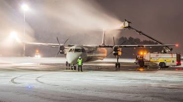 Przygotowania do sezonu zimowego rozpoczynają się na lotnisku w Pyrzowicach już w połowie wakacji. Cały sprzęt gotowy jest we wrześniu. Od tej pory czeka na ewentualny śnieg i przymrozki. Co trzeba zrobić, kiedy samolot zamarznie? </p>  Podczas opadów śniegu samoloty muszą zostać oczyszczone przed startem. Tym właśnie zajmuje się m.in. firma LS Airport Services. Samolot zostaje skierowany na miejsce przygotowane do odladzania. Właśnie po to dwa lata temu powstała nowa płyta o powierzchni 40 tys. m kw. - W zimie samoloty nie są myte, lecz są oczyszczane z zanieczyszczeń typu lód, śnieg czy szron. Musimy też zapewnić wystarczającą ilość potrzebnego płynu do odladzania samolotów - mówi Sebastian Grochala, rzecznik prasowy LS Airport Services. </p> Dlaczego odladzanie samolotów jest takie ważne i czemu czasami powoduje opóźnienie startu? Powierzchnie skrzydeł, stateczników oraz kadłuba muszą być bowiem gładkie. - Samo odlodzenie jest jednak skomplikowanym procesem, który czasami faktycznie opóźnia start - mówi Grochala. </p> Niska temperatura nie jako jedyna wpływa na oblodzenie samolotu. Elementy samolotu przy wietrze czy długim postoju potrafią obniżyć swoją temperaturę. W efekcie oszronienie, a nawet lód gotowe. Kolejnym zagrożeniem jest przechłodzone paliwo w samolocie, który na wysokości przelotowej leci w temperaturze około -40 stopni C. </p> Odladzanie można wykonywać z pasażerami na pokładzie. Proces rozpoczyna się od statecznika. Następnie odladza się kadłub, a na końcu skrzydła. - Używamy specjalistycznych płynów nawet do temperatury -33 stopni. Rozprowadzają go specjalne pojazdy. Jeśli pada śnieg, to po oczyszczeniu dodatkowo zabezpieczamy samolot innym płynem, tak gęstym, że śnieg gromadzi się na jego powierzchni. Przy starcie ta warstwa płynu odpada, ale trzeba się śpieszyć. Płyn spełnia swoje zadanie od kilku do kilkudziesięciu minut - mówi Grochala. </p> Odladzanie samolotów to wielkie widowisko przede wszystkim dla spotterów.  Grupa Miłośników Katowice A