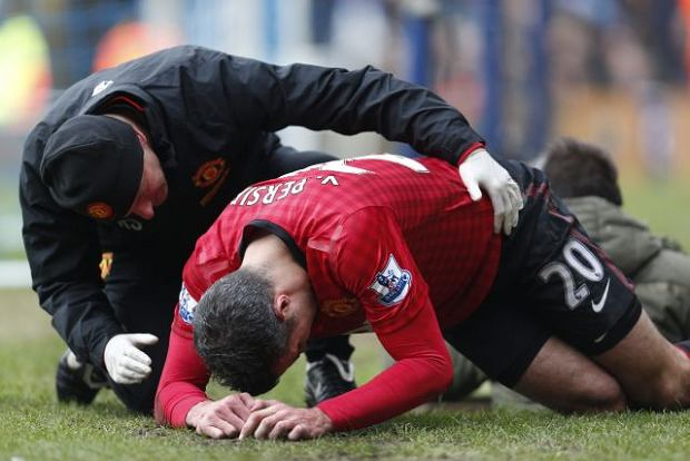 Manchester United's Robin Van Persie is helped after he was injured during a Premier League soccer match against Queens Park Rangers, at Loftus Road ground in London, Saturday, Feb. 23, 2013. Manchester United won the match 2-0. (AP Photo/Lefteris Pitarakis)